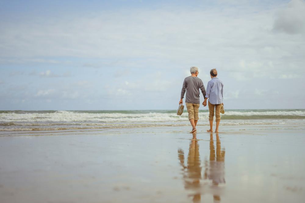 Couple marchant sur la plage au lever du soleil